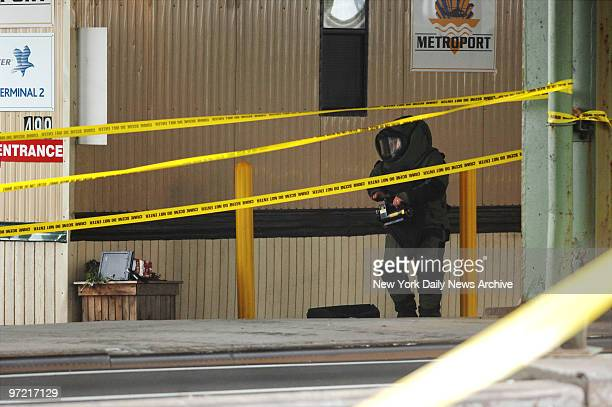 A bomb squad technician investigates a suspicious package at the 34th St heliport at the FDR Drive