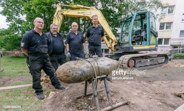 Bomb technicians Norbert Gaethje Georg Ocklenburg Heinz Kollath and Oliver Kinast pose next to a US 500 kilo bomb from Second World War which the...