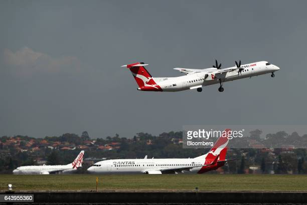 A Bombardier Inc Q400 aircraft operated by QantasLink regional carrier of Qantas Airways Ltd top takes off as a Boeing Co 737800 aircraft operated by...