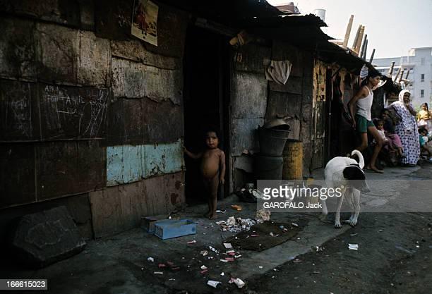Bombay India En Inde au début des années 60 dans un bidonville de Bombay un enfant nu se tient sur le seuil d'une cabane en tôles aux côtés d'un chien