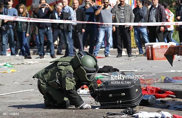 A bombdisposal expert inspects a suitcase at the site of twin explosions near the main train station in Turkey's capital Ankara on October 10 2015 At...