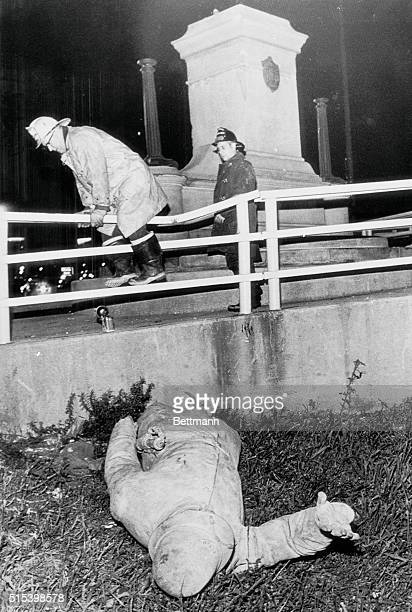 Bombed Again Chicago Illinois Fireman climbs railing to view the Haymarket Square Statue of a policeman that was blown off its pedestal and shattered...