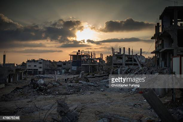 Bombed buildings scar the landscape where families still live amongst the rubble of Gaza on June 11 Gaza City Gaza The devastation across Gaza can...