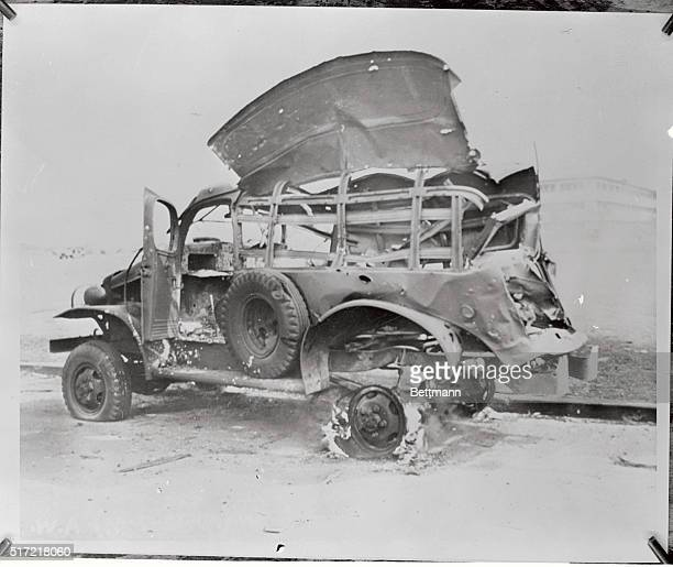 A bombed truck still burns off the Hickam Field Parade Ground at 'F' Street three hours after the first Japanese planes appeared over the Hawaiian...