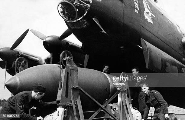 "Bomber command load one of the new 12,000 pound ""earthquake"" bombs onto a Lancaster II bomber, the same bombs that sunk the 45,000 ton German..."