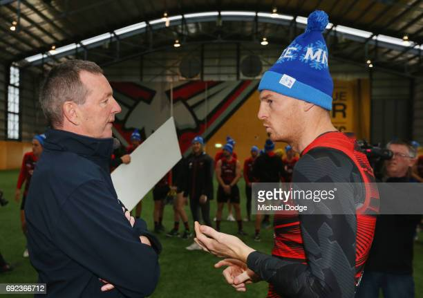 Bombers legend Neale Daniher listens to Brendon Goddard of the Bombers during a cheque presentation to fight MND at the Essendon Football Club on...