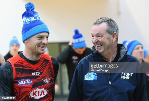 Bombers legend Neale Daniher listens to Brendon Goddard of the Bombers before a cheque presentation to fight MND at the Essendon Football Club on...