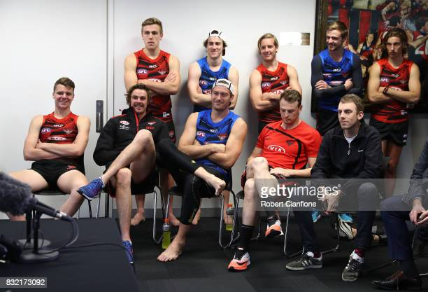 Bombers player look on as James Kelly of the Bombers speaks to the media during a press conference to announce his retirement at the Essendon...