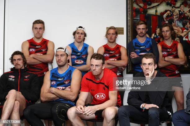Bombers players look on as James Kelly of the Bombers speaks to the media during a press conference to announce his retirement at the Essendon...