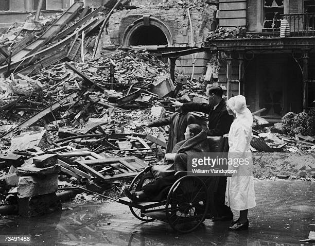A bombing victim in a wheelchair is shown around the site of an air raid which destroyed three ward blocks at St Thomas' Hospital London 9th...