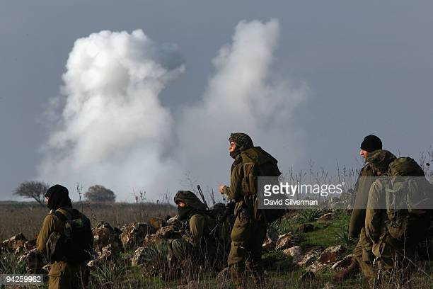 Bombs explode on a target range as Israeli army paratroopers advance during their livefire training exercise December 10 2009 on the Golan Heights...