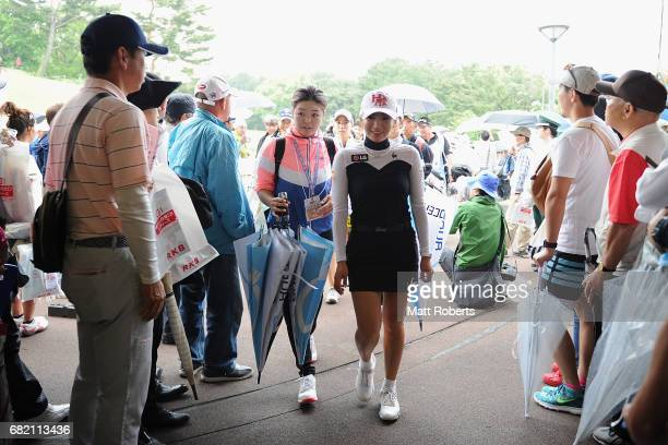 BoMee Lee of South Korea leaves the course as play is suspended due to servere thunderstorms during the first round of the HokennoMadoguchi Ladies at...