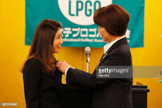 BoMee Lee of South Korea receives a lapel pin from LPGA president Hiromi Kobayashi during the Ladies Professional Golfers' Association of Japan...