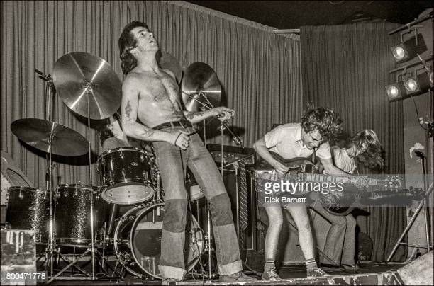 Bon Scott Angus Young and Mark Evans of AC/DC performing on stage Nashville Rooms London on May 27 1976