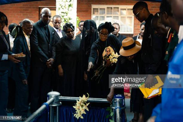 Bona Mugabe Chikore daughter of former Zimbabwe president Robert Mugabe throws flowers ontop of her fathers coffin next to her mother Grace Mugabe...