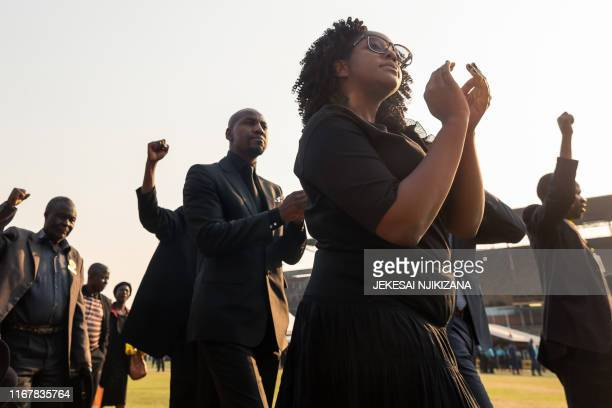 TOPSHOT Bona Mugabe Chikore daughter of late former Zimbabwean president Robert Mugabe salutes the crowd gathered for viewing the body of Robert...