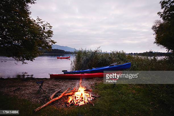 bond fire at a lake with canoe - lakeshore stock pictures, royalty-free photos & images