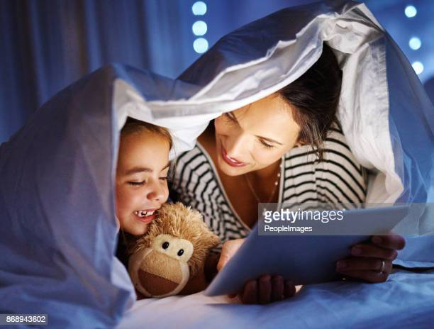 bonding at bedtime - super mom stock photos and pictures