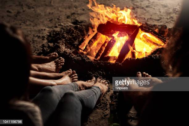 bonding by the bonfire - bonfire stock photos and pictures