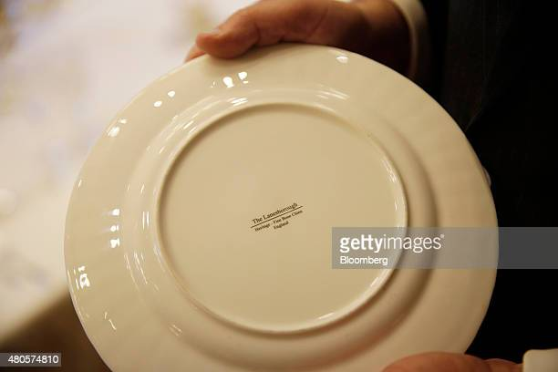A bone china plate is held for a photograph in the dining room inside the Lanesborough luxury 5star hotel operated by the Oetker Group in London UK...
