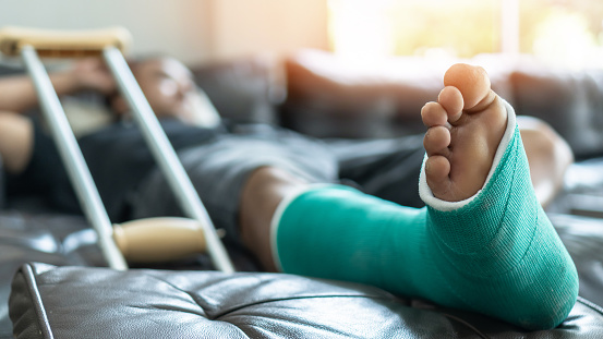 Bone fracture foot and leg on male patient with splint cast and crutches during surgery rehabilitation and orthopaedic recovery staying at home 1170192288