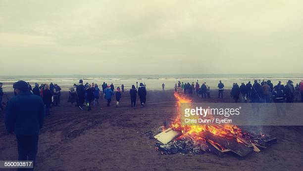 Bonfire Amidst People On Beach Against Sky
