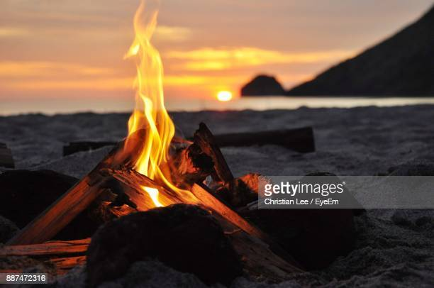 bonfire at beach during sunset - bonfire stock photos and pictures