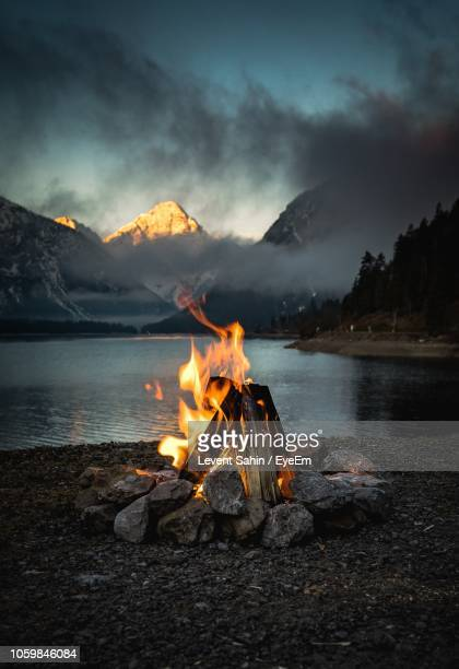 bonfire at lakeshore against sky during sunset - campfire stock pictures, royalty-free photos & images