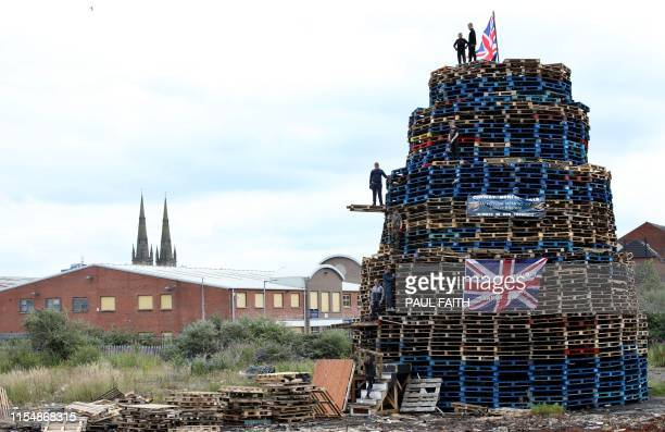 Bonfire builders complete their structure near the peace wall in west Belfast Northern Ireland ahead of the traditional 11th night bonfires on July 9...