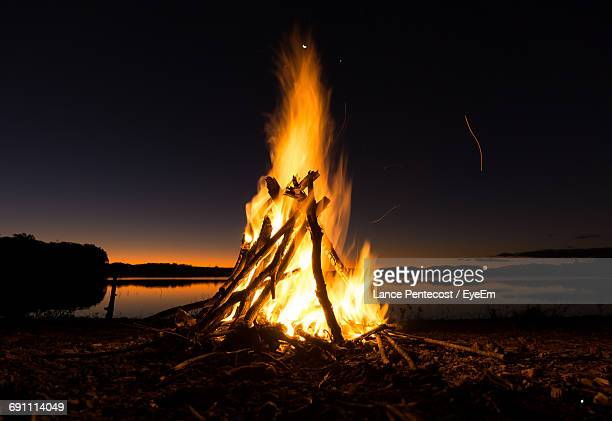 Bonfire On Beach Against Sky At Night