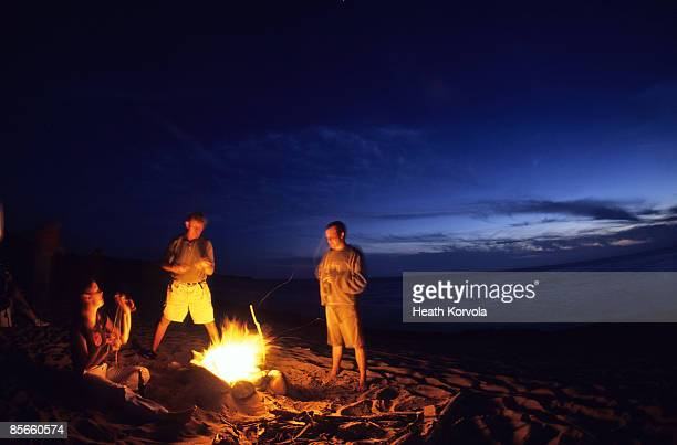 Bonfire on beach with ocean in background.
