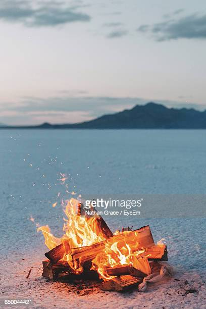 bonfire on snowy field against sky at dusk - bonfire stock photos and pictures