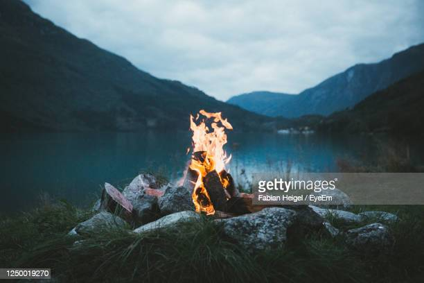 a bonfire we made while camping somewhere close to an idylic lake in norway. - キャンプファイヤー ストックフォトと画像