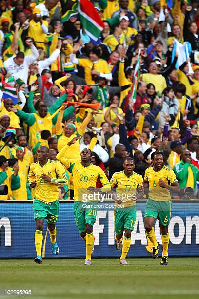 Bongani Khumalo of South Africa celebrates scoring the opening goal with team mates during the 2010 FIFA World Cup South Africa Group A match between...