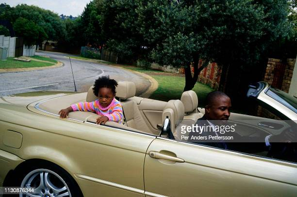 Bongani Mkhatshanes age 32 reverses his BMW 330CI Convertible with his daughter in the backseat on April 25 2005 in Johannesburg South Africa Bongani...