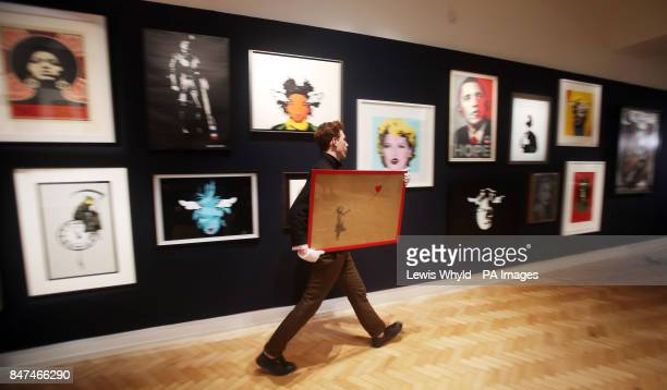 A Bonham's employee carrying Banksy's Girl and Balloon 2009 that is estimated to fetch pound15000 pound25000 during their Urban Art auction next week