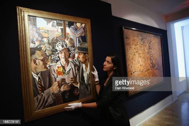 Bonhams employee poses beside a piece of work by Australian artist Herbert Badham entitled 'Travellers', 1933 at Bonhams auction house on May 7, 2013...