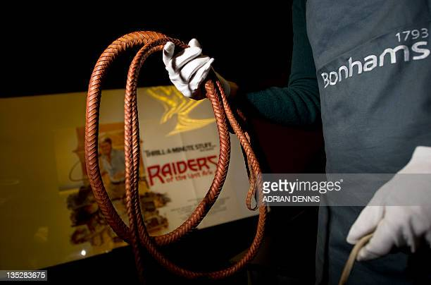 Bonham's employee poses holding the bullwhip used by US actor Harrison Ford in his role as Indiana Jones in the 1981 film Raiders of the Lost Ark...
