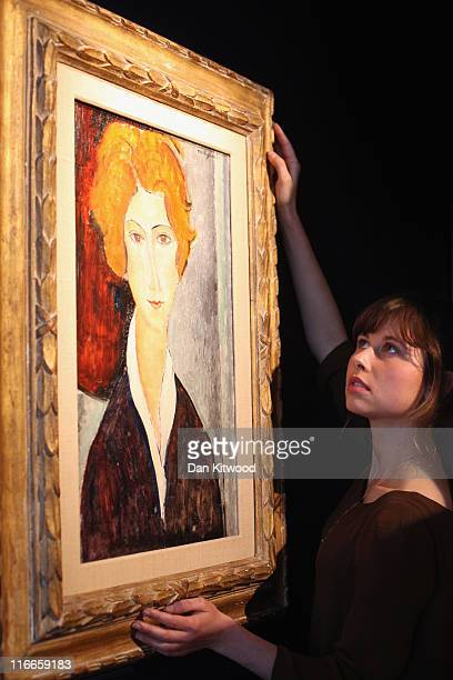 Bonhams intern Diana Kurakina poses with a work by Amedeo Modigliani entitled 'Portrait de Femme' at Bonhams Auction Houses on June 17, 2011 in...