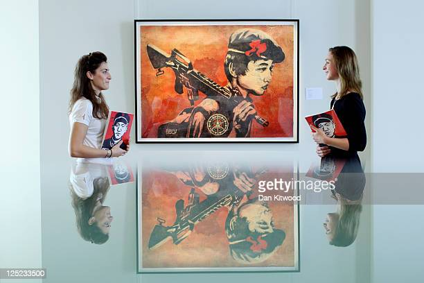 Bonhams interns stand beside a work entitled 'Duality of Humanity II' by Shepard Fairey at Bonhams Auction house on September 16 2011 in London...