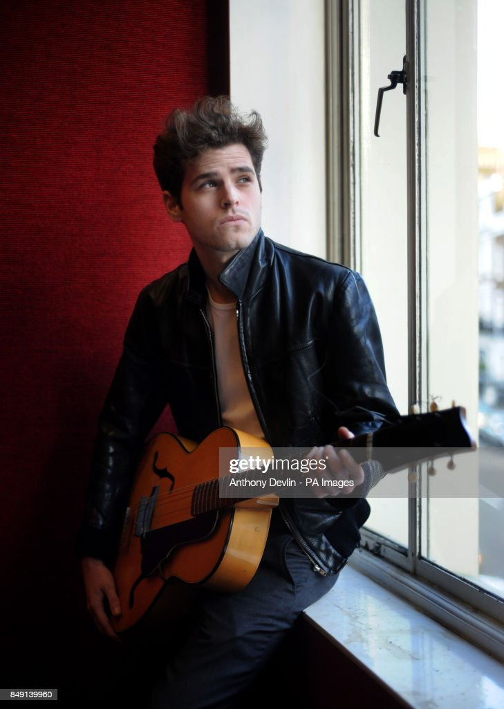 Bonhams' Porter Harry Woodlock poses with a Hamburg era leather jacket and guitar belonging to George Harrison during a photocall to publicise the upcoming Entertainment Memorabilia sale at Bonhams auction house in central London.