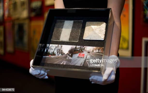A Bonhams staff member holds a boxed piece of the original Abbey Road crossing from when the road was replaced in 1994 during a photocall at Bonhams...