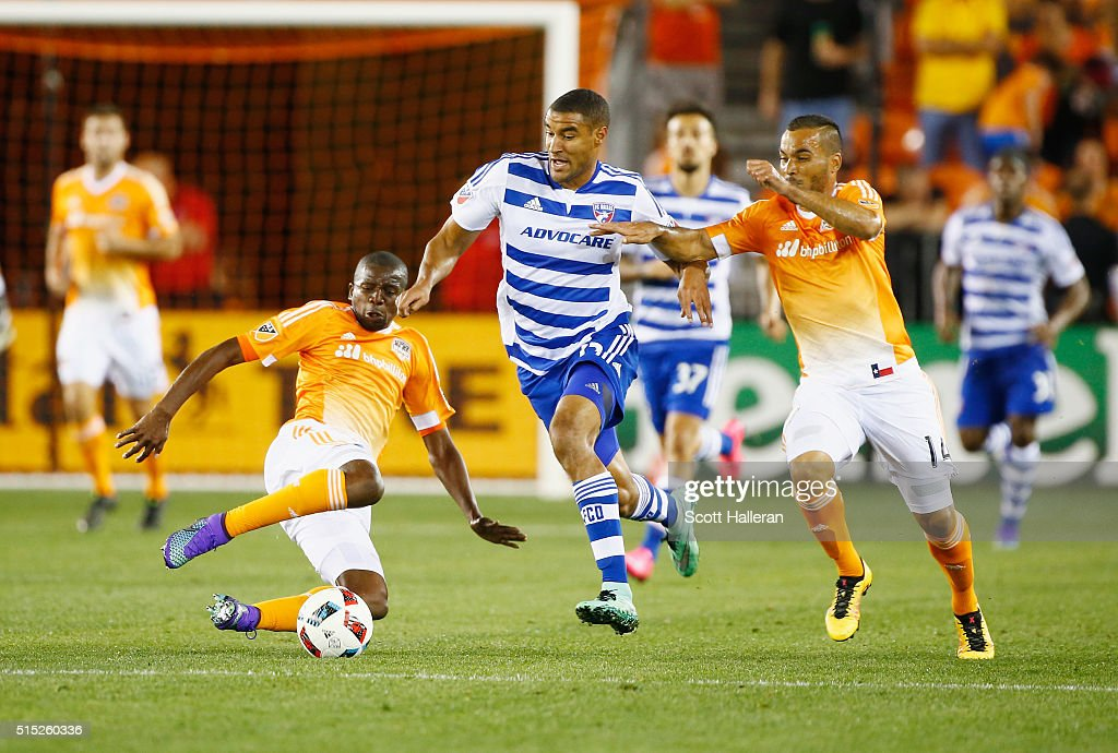 Boniek Garcia #27 and Alex #14 of the Houston Dynamo battle for the ball with Tesho Akindele #13 of FC Dallas during their game at BBVA Compass Stadium on March 12, 2016 in Houston, Texas.