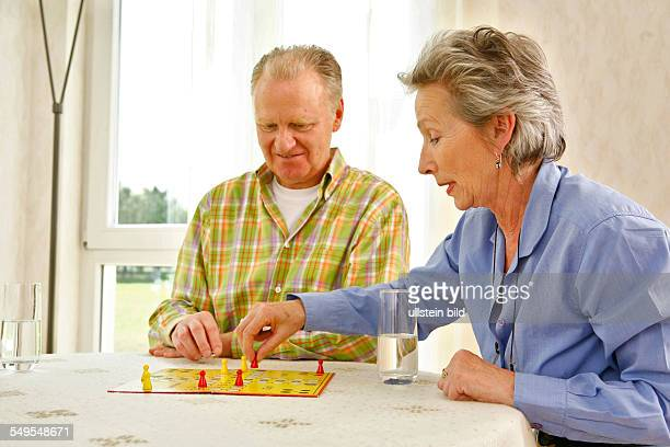 Living in old age Seniors couple playing ludo board game at home