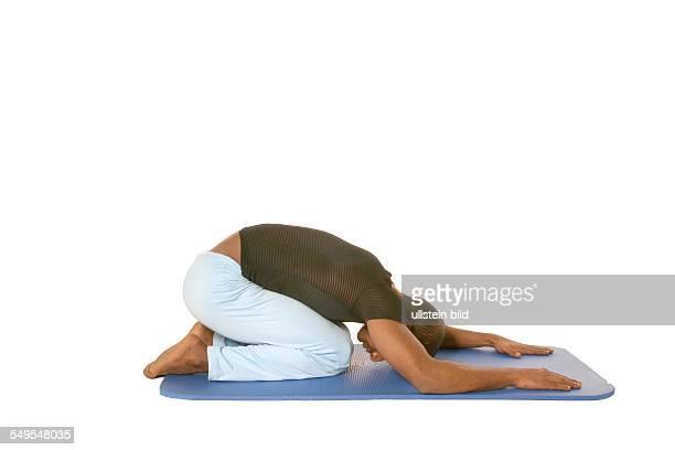 Runden Sie den Ruecken und lassen Sie Ihren Oberkoerper auf die Matte gleiten Die Unterarme zeigen nach vorn