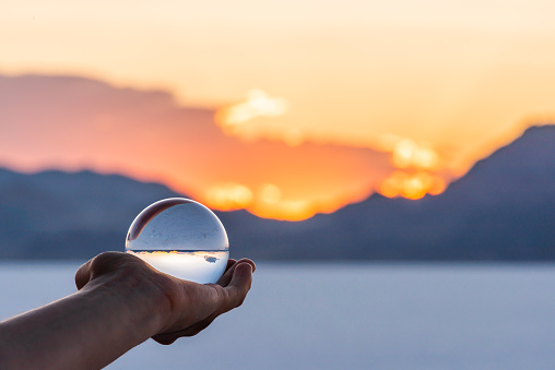 Bonneville Salt Flats colorful landscape bokeh background with hand holding crystal ball near Salt Lake City, Utah and mountain view and sunset 1177726831