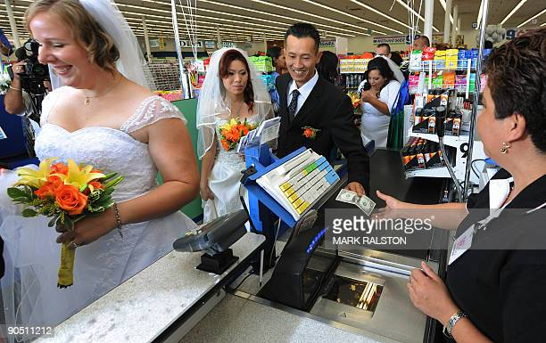 Bonnie Cam and Jon Nguyen pay for their 99 cent wedding ceremony at a checkout at the 99 cent store in Los Angeles on September 9 2009 The budget...