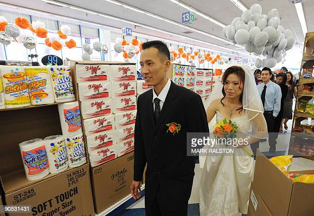 Bonnie Cam and Jon Nguyen walk down the food aisle after their 99 cent wedding ceremony at the 99 cent store in Los Angeles on September 9 2009 The...