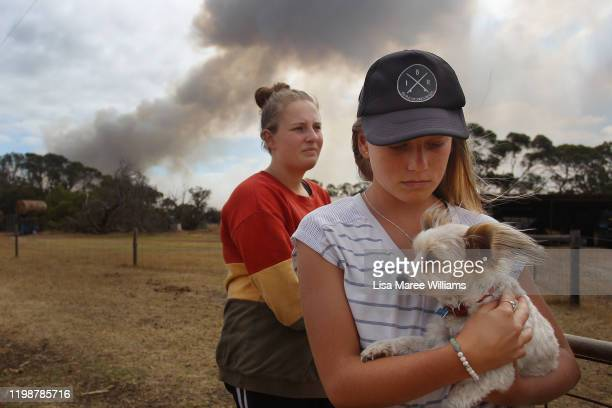 Bonnie Morris and sister Raemi Morris look on as their family and CFS firefighters battle bushfires at the edge of their family farm on January 11...