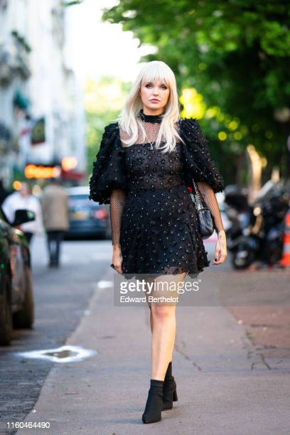 """Bonnie Strange wears a black puff sleeves dress with black fabric flowers embroideries, a black Chanel bag, black sock boots, outside the """"Scandal A..."""